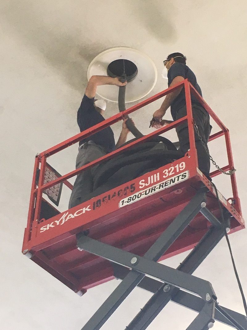 Duct Squads air vent cleaning professionals cleaning and airvent on a scissor lift
