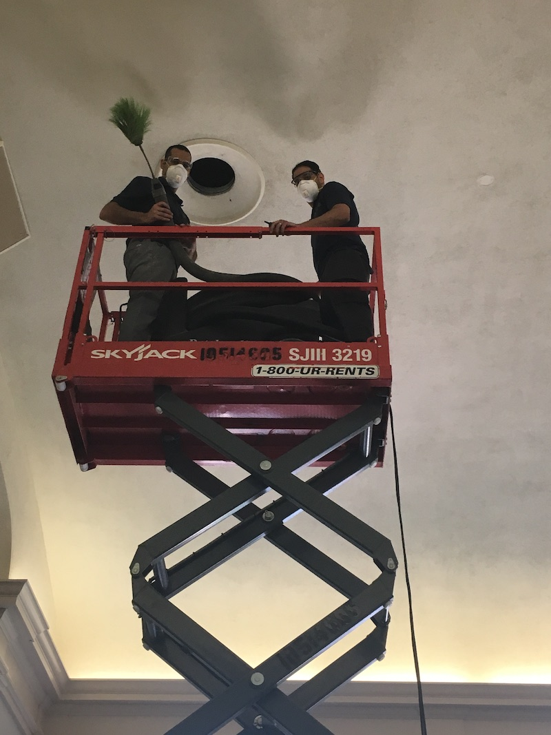 Duct Squads air vent cleaning professionals cleaning and air vent on a scissor lift